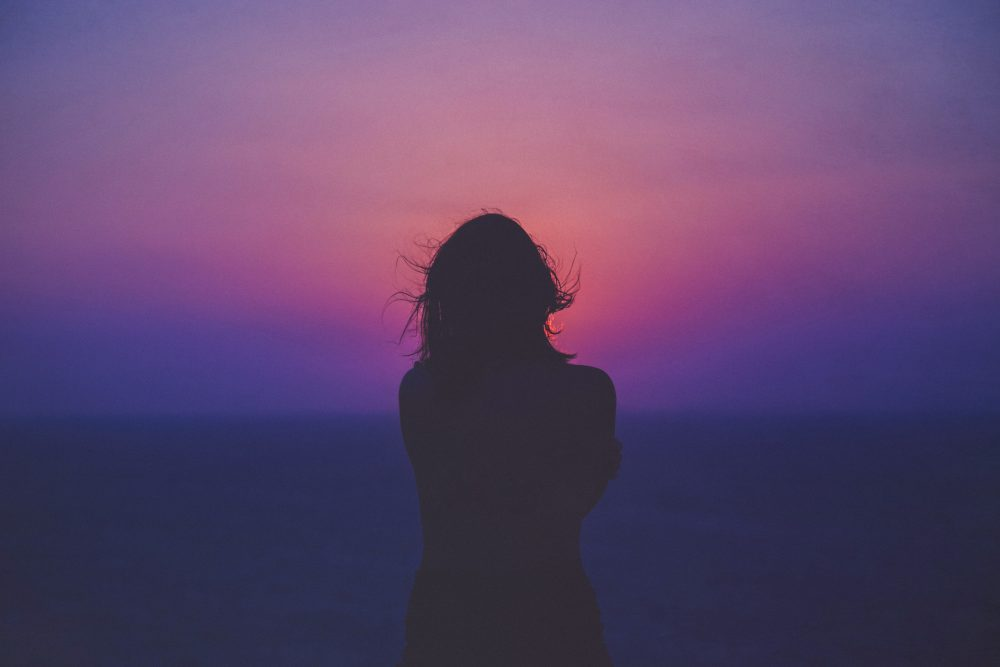 silouette of woman watching pink and purple sunset